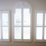 Inside view of 3 side by side windows with custom shutters white walls