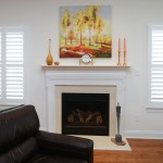 Fireplace with painting above it two windows with custom shutters