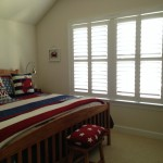 A bedroom with windows that have plantation shutters from A Shade Above Millville DE