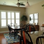 View of custom shutters in kitchen with table and counter